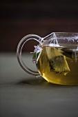 Grüner Tee mit Teebeuteln in Glasteekanne
