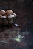 Fresh eggs in a wire basket on a wooden surface
