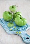 Grüne Tomaten auf einem blauen Schneidebrett