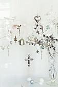 Glasvase mit silbern glänzendem Weihnachtsschmuck an weiss gefärbten Zweigen