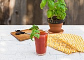 A glass of vegetable juice garnished with basil on a garden table