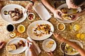 Leute frühstücken Nachos, Sandwiches und Pancakes (USA)
