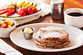 Blueberry pancakes with icing sugar, coffee and fruit