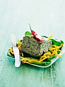 A slice of broccoli terrine with chilli peppers on a yellow pepper salad