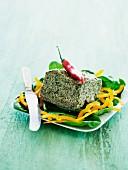 Ein Stück Brokkoliterrine mit Chilischote, auf Salat mit gelben Paprika