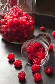 Wild raspberries spilling out of a glass
