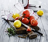 An arrangement of tomatoes and lemons on a wooden surface