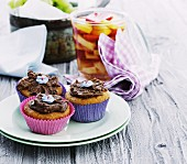 Three muffins with chocolate cream and sugar flowers