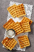 Waffles and a sieve of icing sugar on a doily