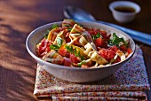 Pasta salad with colourful butterfly pasta, tomatoes and rocket