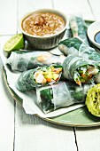 Rice paper rolls filled with vegetables served with lime and a peanut dip