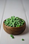Frozen peas in a wooden bowl