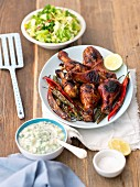 Grilled chicken drumsticks with chilli peppers and cucumber raita