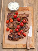 Grilled pork collar with cherry tomatoes and tzatziki