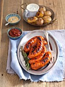 Grilled sausage with baked potatoes and sauces