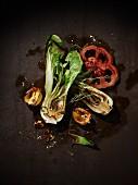 Gegrilltes Gemüse auf braunem Metalluntergrund (Paksoi, rote Paprika, gelbe halbierte Habaneros) mit Thymianzweig