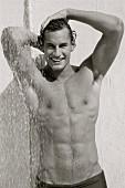 Junger, sportlicher Mann unter der Dusche