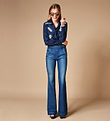Frau in Schlaghose, bestickter Bluse, Sonnenbrille und High Heels im Retro-Look