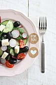 A salad of cucumbers, tomatoes, olives, radishes and feta cheese