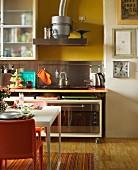 Wohnküche mit schwebender Arbeitsplatte und Rollschrank darunter; gedeckter Essplatz mit orangefarbenen Stühlen im Vordergrund
