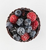 A chocolate cupcake with berries and icing sugar