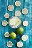 A glass of water with lots of limes
