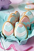 Egg-shaped biscuits with pastel-coloured icing for Easter