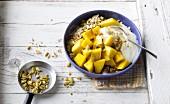 Exotic wholemeal muesli with mango, soya yoghurt and roasted pine nuts