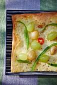 A mozzarella, grape and pepper pizza