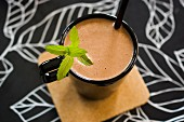 Cocoa in a black cup with a straw and a mint garnish