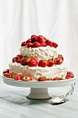 A strawberry cake with cream on a cake stand