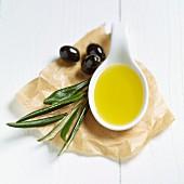 Ein Löffel Olivenöl, Olivenblätter und schwarze Oliven auf Papier