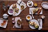 Vollkorn-Tramezzini mit Räucherforelle, Pumpernickel mit Schinken und Preiselbeerbutter, Thunfisch-Baguette mit Ei und Curry, Landbrot-Schnitte mit Camembert und Apfelspalten