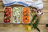 A trio of vegetable salads on a rustic wooden table