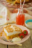 A slice of lemon meringue cake and homemade lemonade for a party