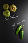 Tomatillos and jalapeños on a slate surface with labels