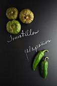 Tomatillos und Jalapenos auf Schiefertafel mit Schrift