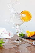A splashing glass of water and a slice of orange
