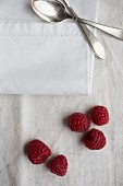 Fresh raspberries, a spoon and a napkin on a linen cloth