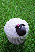 An Easter lamb cupcake on a grass surface