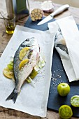 Porgy with green tomatoes and garlic on parchment paper