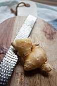 Fresh ginger root with a grater on a chopping board