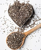 Chia seeds in a heart-shaped mould and on a wooden spoon