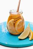 A jar of honey with lemon slices