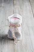 A preserving jar in a paper bag tied with a ribbon