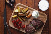 Beef steak with potatoes, cherry tomatoes and sour cream