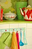 Küchenutensilien an Wandhakenleiste, unter grün lackierter Ablage, darauf Retro Kanne und Gefäss aus Emaille