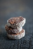 A stack of three chocolate and almond biscuits with a sugared rim