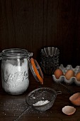 A jar of flour, a metal sieve, eggs and baking tins