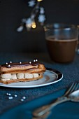 A chocolate covered eclair with silver pearls and coffee cream in front of a cup of coffee (Christmas)